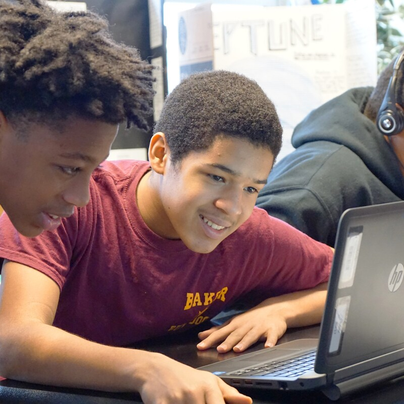Students use a laptop in a classroom while working together on a coding project.