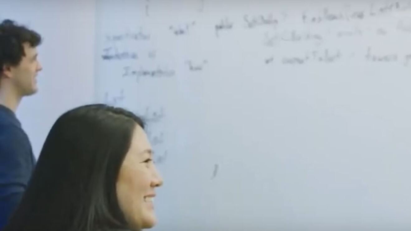 A woman in a classroom setting smiles as she looks to her right. Behind her, a man writes on a white board.