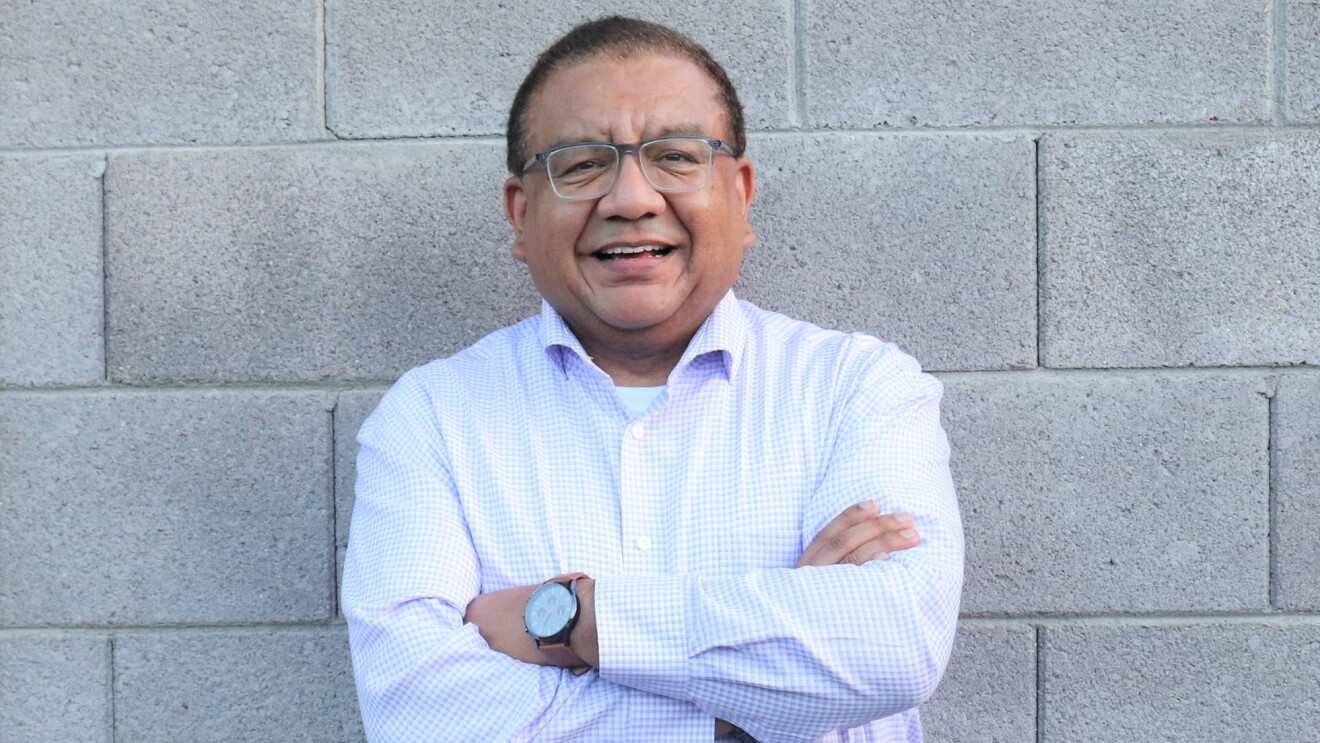 An image of a man smiling for a photo while folding his arms while standing in front of a cement brick wall.