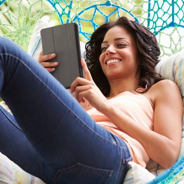 A woman lays in a swing while watching content on her tablet.