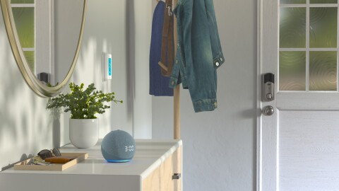 An entryway of a home has a coat rack as you walk in the door. There is a dresser with a mirror on the wall behind it. On the dresser is a Amazon Dot showing the time, a small plant and a tray holding keys, sunglasses and a wallet.