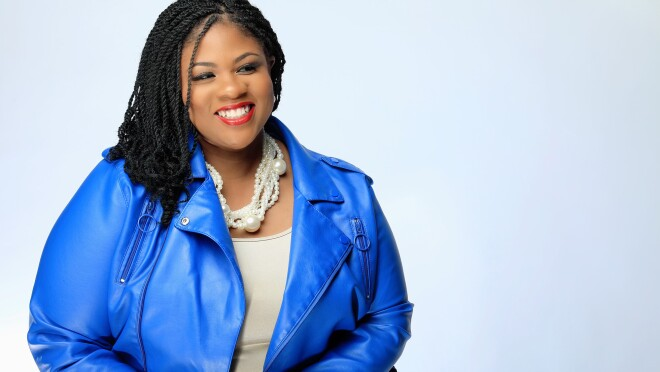 An image of a woman sitting on a chair, smiling for a photo against a white background while wearing a bright blue blazer.