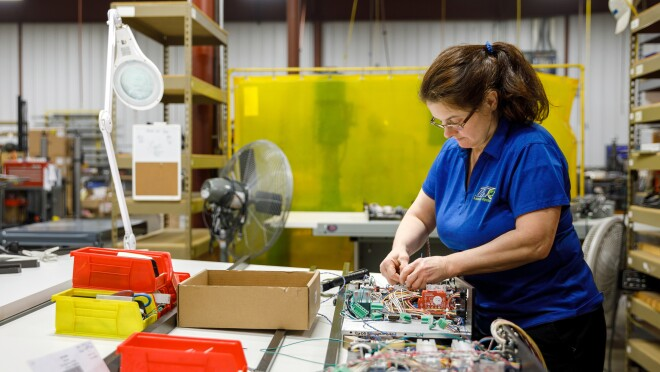 A woman in a blue polo shirt and black pants stands at a work table and assembles electronics.