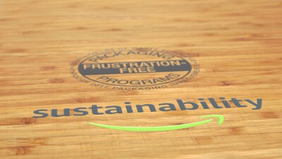 A wooden table has the Amazon Frustration Free Packaging Seal with the Amazon Sustainability logo.