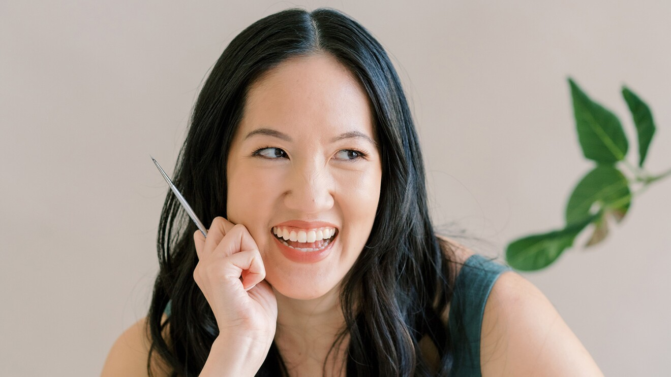 An image of a woman smiling for a photo while leaning her face on her hand and looking away. She is holding a pencil in one hand.