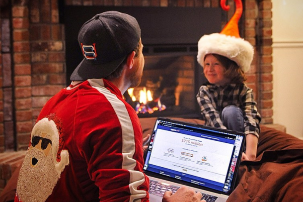 A man sits with his child while looking at a laptop. The child is wearing an elf hat and the man is wearing a Santa jacket.