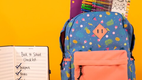 """A brightly colored backpack filled with pens, a folder, and more, sits in front of a yellow background. To the right is a notepad that has writing on it that says """"Back to school checklist, backpack, books, stationary, lunchbox"""""""