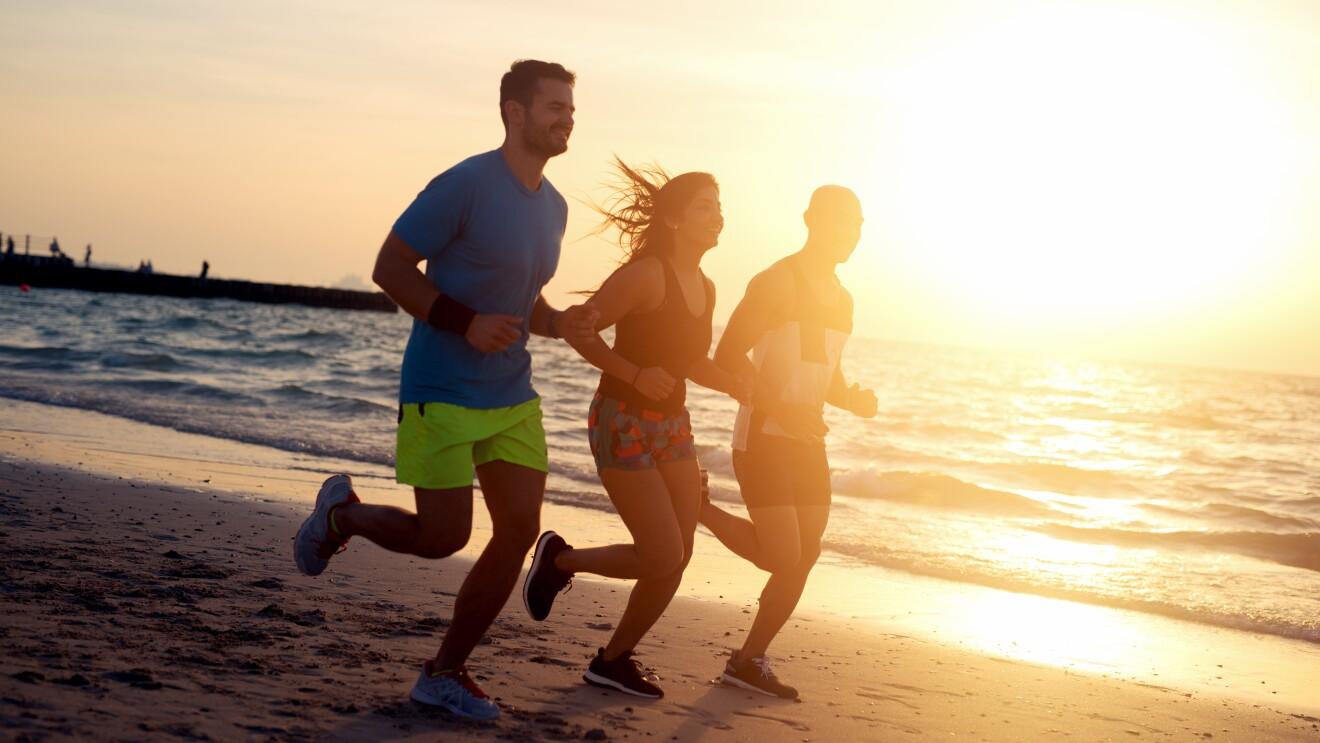 Two men and a woman run on a beach at sundown.